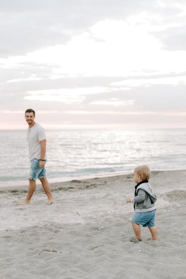 Adorably Perfect Young Father and Baby Toddler Son Family Having Fun Time at the Sandy Beach During Sunset Outside By the Ocean Wa royalty free stock image