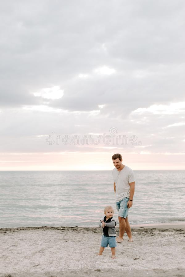 Adorably Perfect Young Father and Baby Toddler Son Family Having Fun Time at the Sandy Beach During Sunset Outside By the Ocean Wa stock images