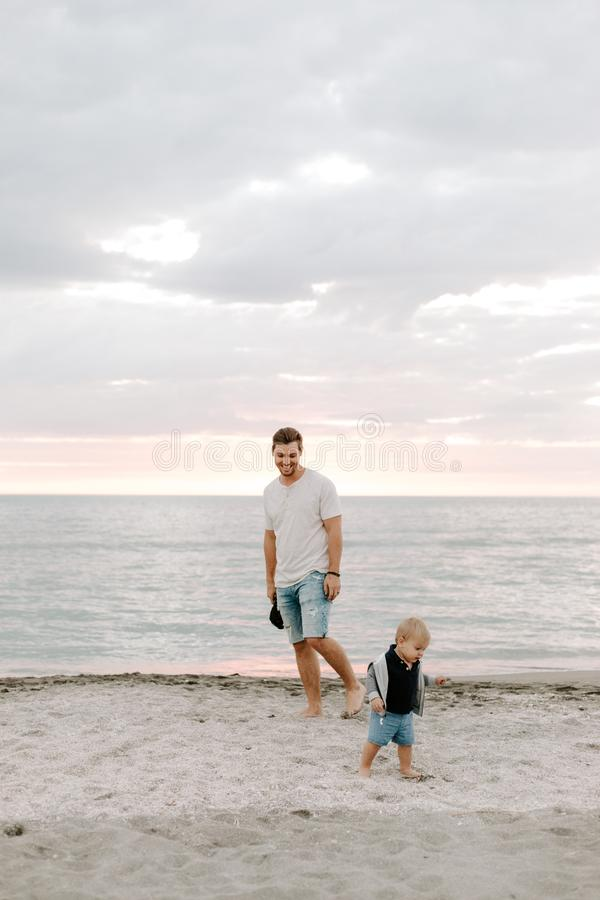 Adorably Perfect Young Father and Baby Toddler Son Family Having Fun Time at the Sandy Beach During Sunset Outside By the Ocean Wa royalty free stock photo