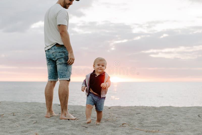Adorably Perfecte Jonge Vader en de Zoonsfamilie die van de Babypeuter Prettijd hebben in Sandy Beach During Sunset Outside door  royalty-vrije stock afbeelding