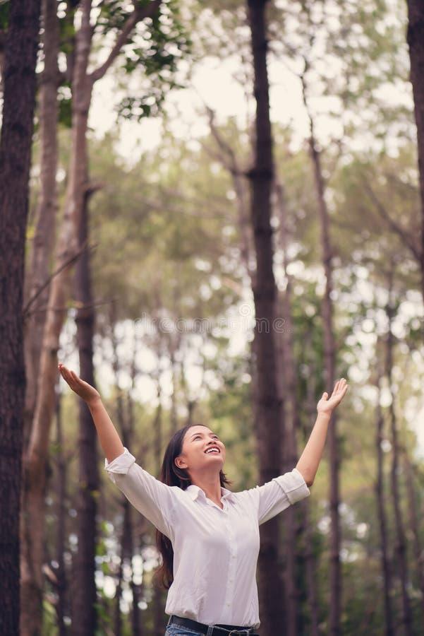 Adoración cristiana con la mano aumentada en el bosque del pino, mujer feliz de foto de archivo libre de regalías