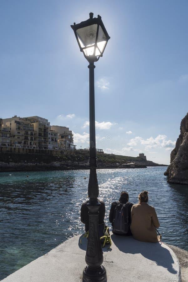 Adoración de Sun y poste de la lámpara en el embarcadero en Xlendi imagenes de archivo