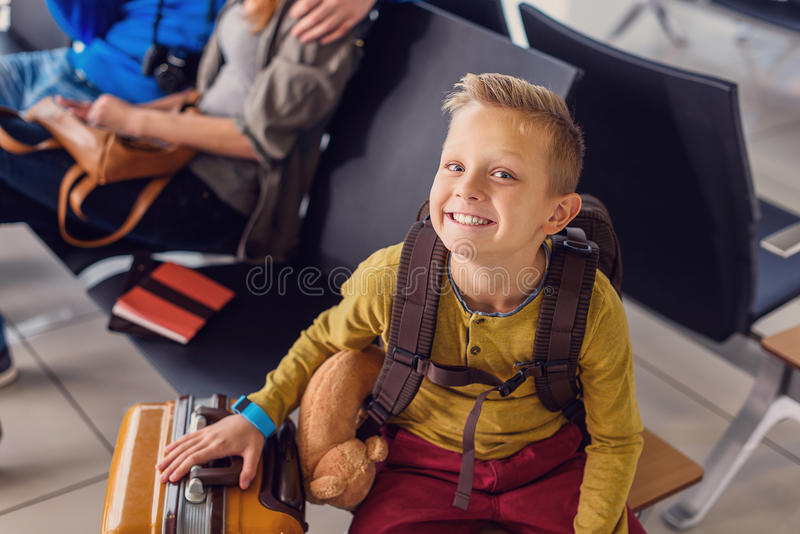 Adoralbe little boy at airport. Happy waiting moments . Top view shot of smiling happy little boy sitting in waiting hall and posing at camera with his parents royalty free stock images