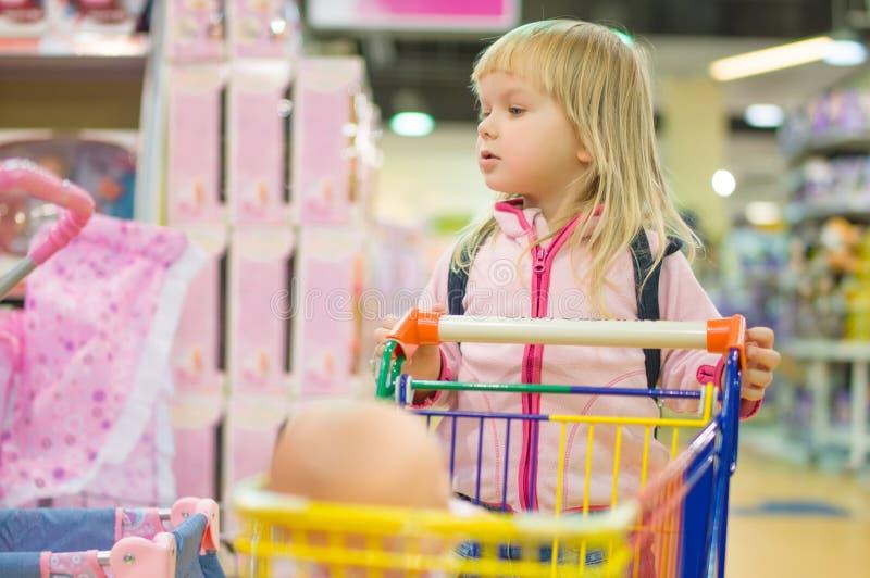 Adorble dziewczyna z małym wózek na zakupy w dzieciaków centrum handlowym zdjęcia royalty free