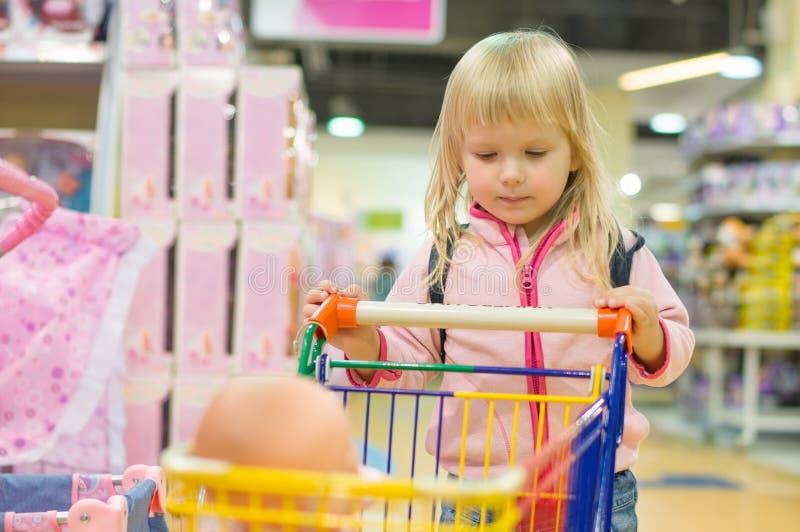 Adorble flicka med den små shoppingvagnen i ungegalleria royaltyfri fotografi