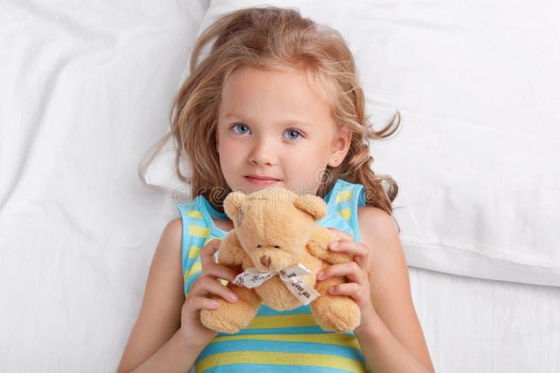 Adorble het kleine jonge geitje met blauwe ogen, licht haar, gekleed in nachthemden, teddybeer in handen houdt, ligt op wit bedde stock foto