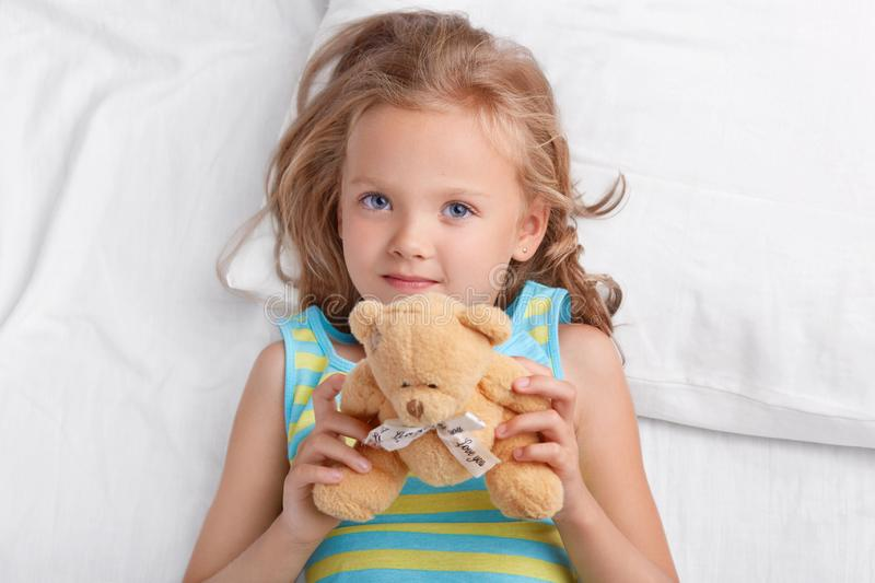 Adorble small kid with blue eyes, light hair, dressed in nightwear, holds teddy bear in hands, lies on white bedclothes, plays wit. H favourite toy in bed stock photo