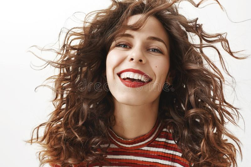 Adore me. Portrait of carefree hot adult woman with curly hair that floats in air, smiling broadly and gazing at camera royalty free stock photo