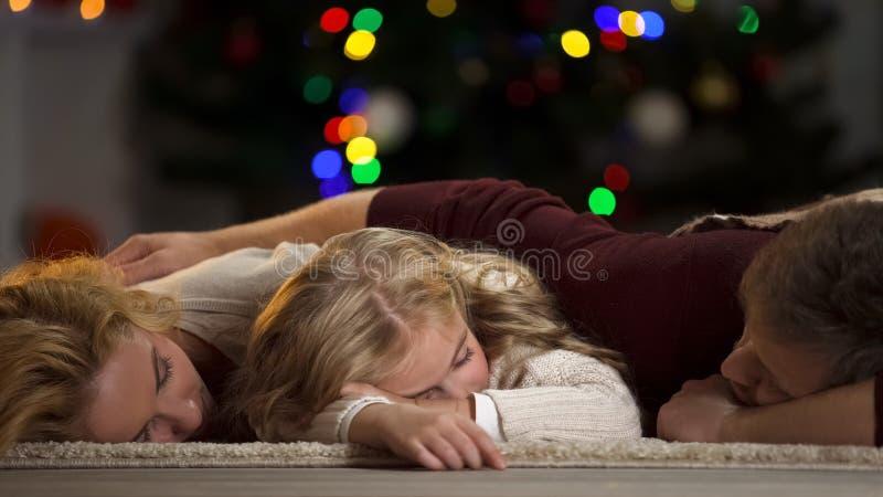 Adormecido caído família sob a árvore de Natal que espera Santa Claus, opinião na mágica fotografia de stock