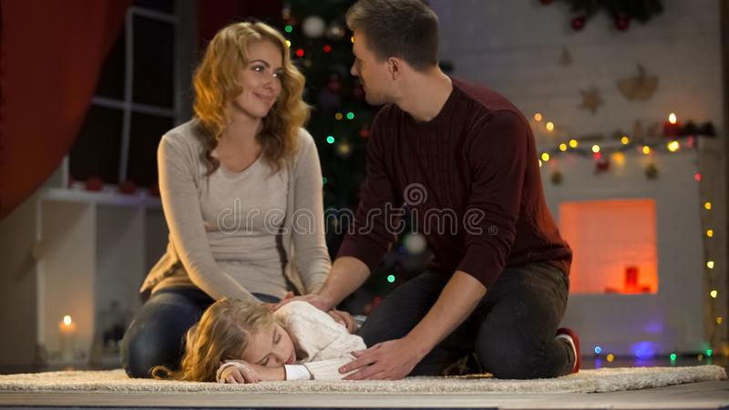 Adormecidos caído sob a árvore de Natal, pais felizes da criança de amor que sentam-se ao lado imagem de stock royalty free