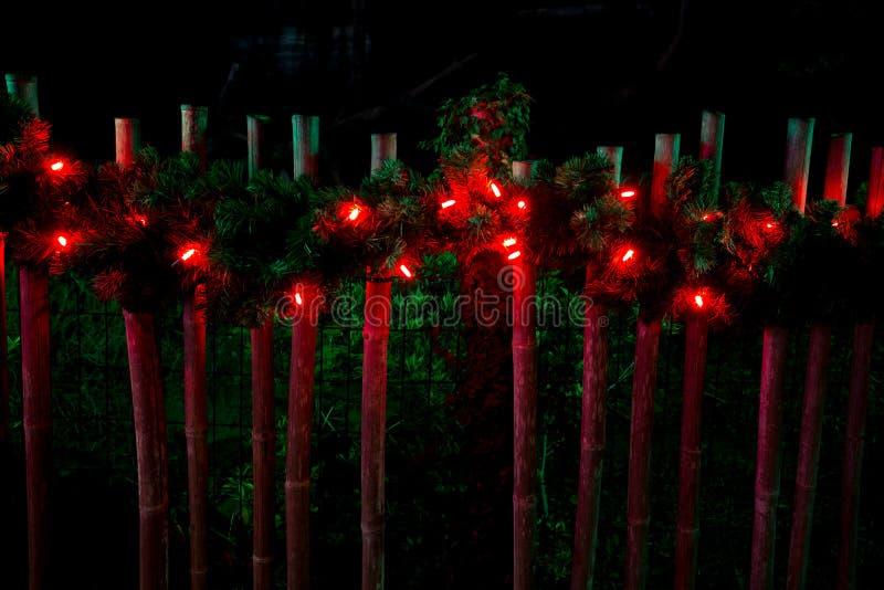 Adornado con las luces rojas de la Navidad en la cerca imágenes de archivo libres de regalías