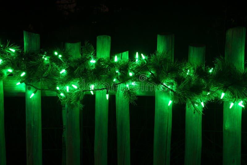 Adornado con las luces verdes de la Navidad en la cerca imagen de archivo