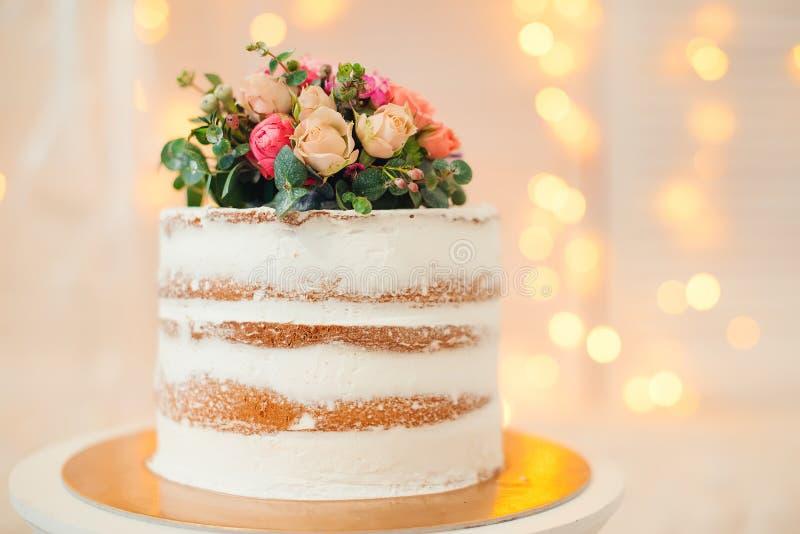 Adornado por la torta desnuda blanca de las flores, el estilo rústico para las bodas, los cumpleaños y los eventos fotos de archivo