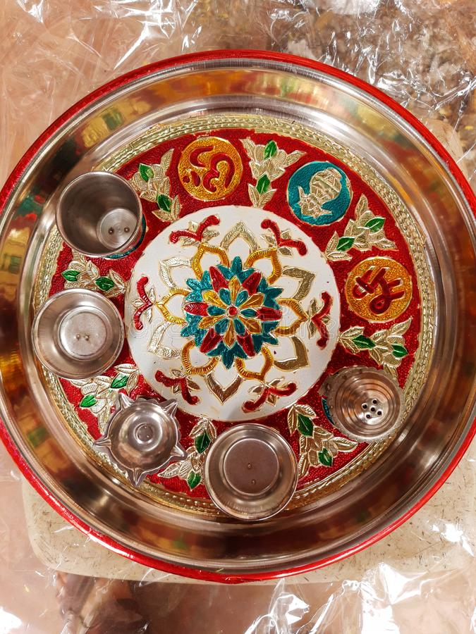 Adorned Indian puja plate containing bowl, a diya and an incense stick stand as well as a shree and a mark of Om. Adorned indian puja plate containing bowl, a stock photos
