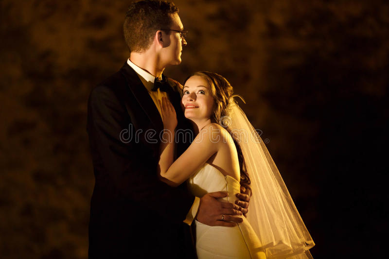 Adorning elegant fashion groom and bride is hugging on the back stock image