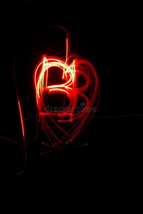 Adorno rojo abstracto del corazón del bb de la pintura de la luz anaranjada en fondo negro imagen de archivo