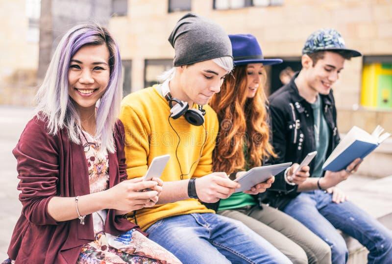 Ados avec les smartphones et le comprimé images libres de droits