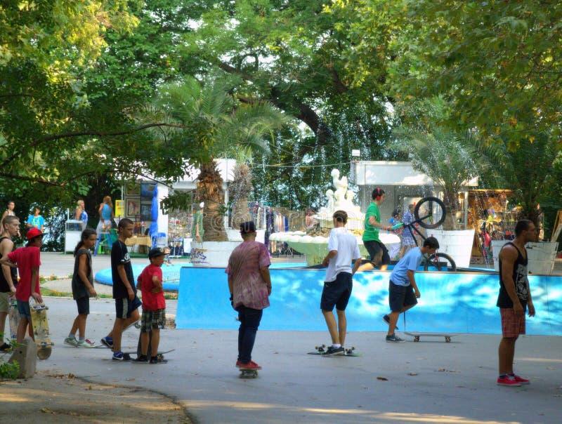 Ados faisant de la planche à roulettes en parc de ville photo stock