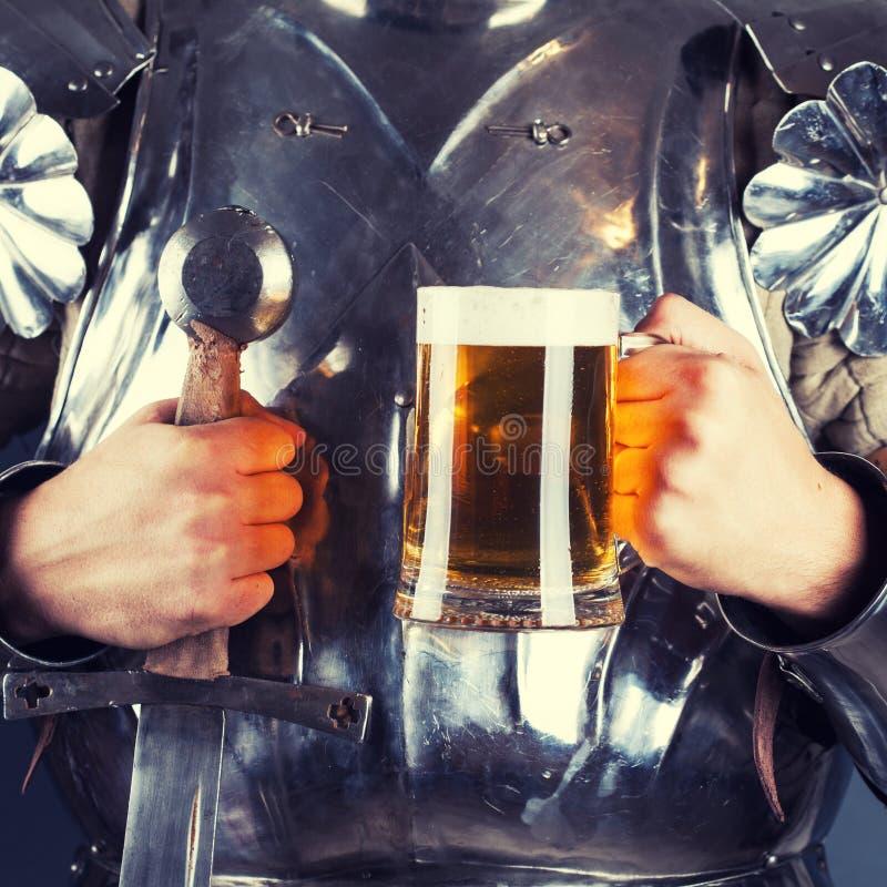 adoubez l'armure de port et tasse de se tenir de bière et de swor à deux mains photo libre de droits