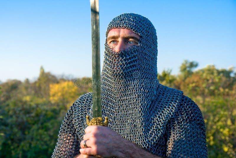 Adoubez l'armure s'usante et retenez sur une épée images stock