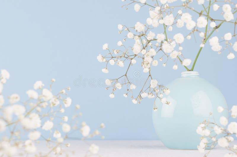 Adoucissez le bouquet élégant de petites fleurs dans la cuvette en céramique de cercle sur le fond bleu en pastel mou image stock