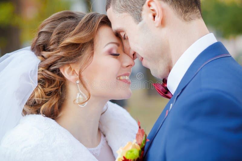 Adoucissez les étreintes et les baisers le marié de jeune mariée photos stock