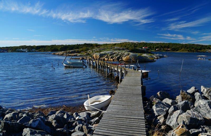 Adoucissez les vagues, les roches nues et un pilier en bois entre deux îles photo libre de droits