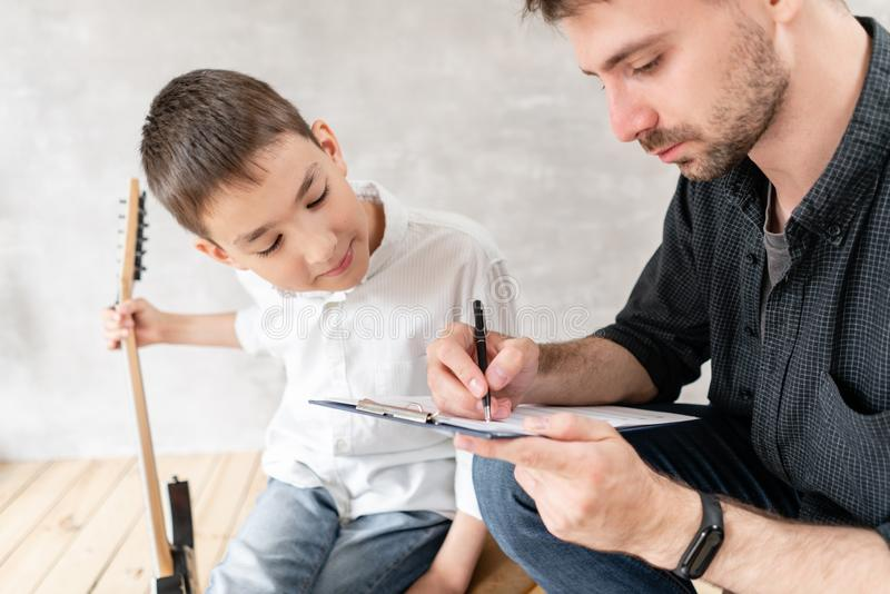 Adoult man writes notes of simple melody on music sheet for his younger brother, who learn to play guitar stock photography