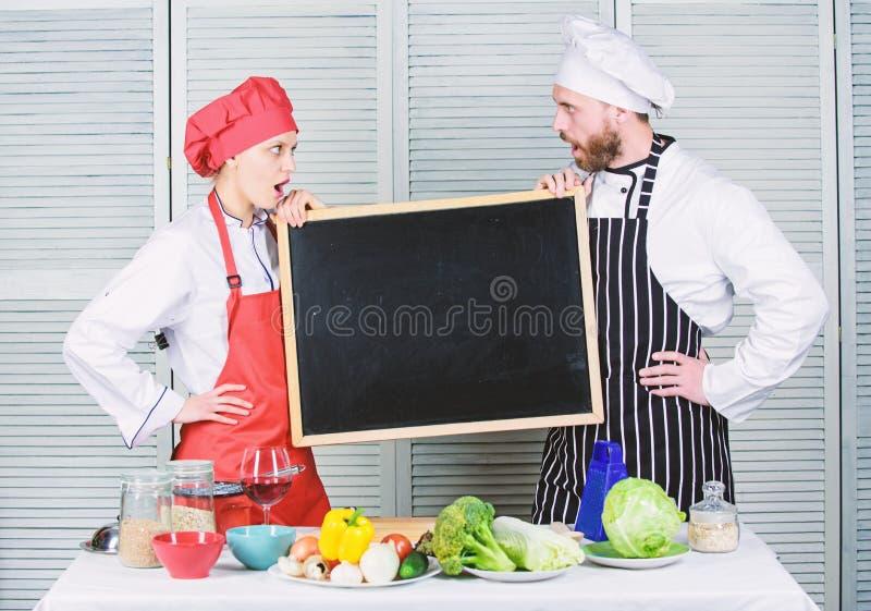 Adquisici?n de una gama de habilidades Pares del hombre y de la mujer que sostienen la pizarra vac?a en cocinar la escuela Cocine fotografía de archivo