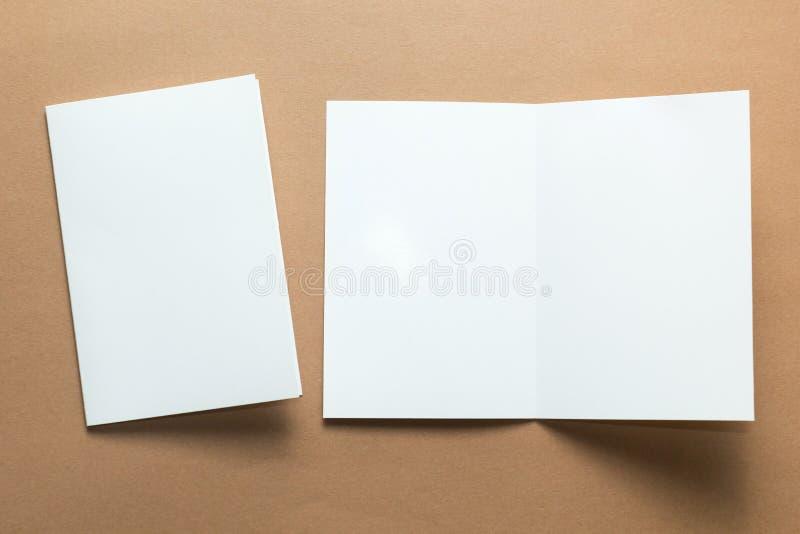 Adreskaartje, brochuretijdschrift op bruine achtergrond, Witboek wordt ge?soleerd dat Model stock foto