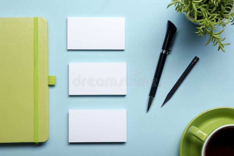 Adreskaartjespatie, blocnote, bloem, koffiekop en pen bij de bovenkantmening van de bureaulijst Het collectieve kantoorbehoeften  royalty-vrije stock foto's