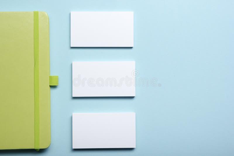 Adreskaartjespatie, blocnote, bloem, koffiekop en pen bij de bovenkantmening van de bureaulijst Het collectieve kantoorbehoeften  royalty-vrije stock afbeelding