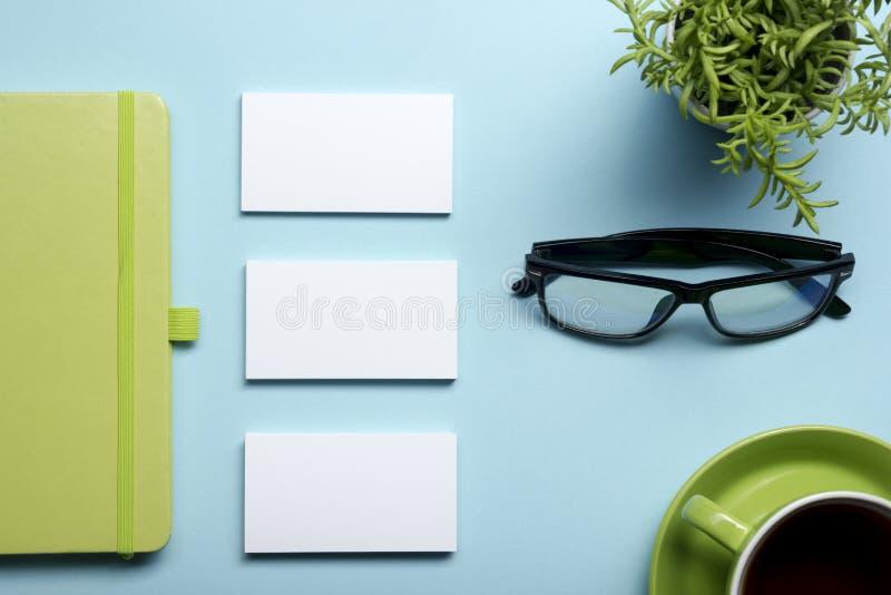 Adreskaartjespatie, blocnote, bloem, koffiekop en pen bij de bovenkantmening van de bureaulijst Het collectieve kantoorbehoeften  royalty-vrije stock foto