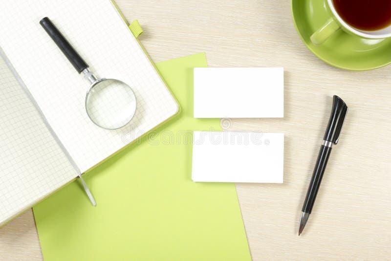 Adreskaartjespatie, blocnote, koffiekop en pen bij de bovenkantmening van de bureaulijst Collectief kantoorbehoeften brandmerkend stock afbeeldingen