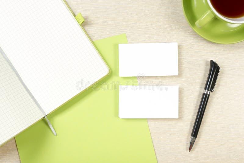 Adreskaartjespatie, blocnote, koffiekop en pen bij de bovenkantmening van de bureaulijst Collectief kantoorbehoeften brandmerkend royalty-vrije stock fotografie