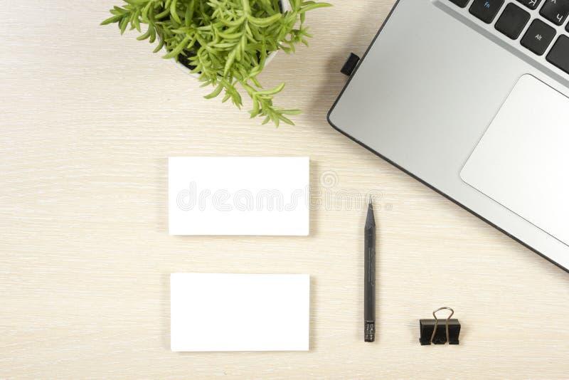 Adreskaartjespatie, laptop, bloem en potlood bij de bovenkantmening van de bureaulijst Collectief kantoorbehoeften brandmerkend m royalty-vrije stock foto's
