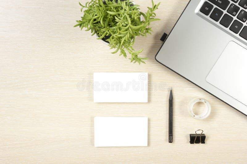 Adreskaartjespatie, laptop, bloem en potlood bij de bovenkantmening van de bureaulijst Collectief kantoorbehoeften brandmerkend m stock fotografie