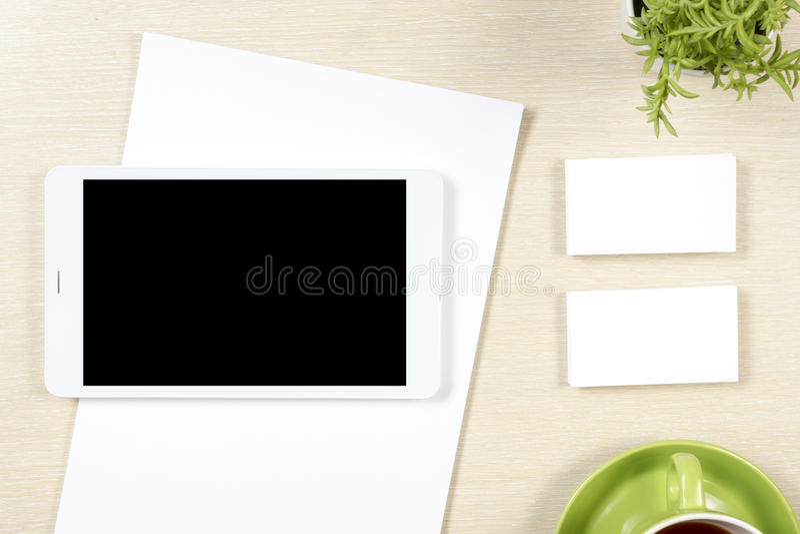 Adreskaartjespatie, smartphone of tabletpc, bloem en koffiekop bij de bovenkantmening van de bureaulijst Collectieve kantoorbehoe royalty-vrije stock afbeeldingen