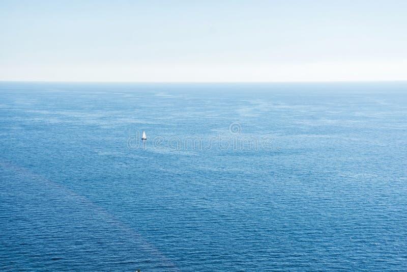 Adriatyckiego morza widok z małą łódką z białym żaglem Spokojny seascape i jasny niebieskie niebo fotografia royalty free