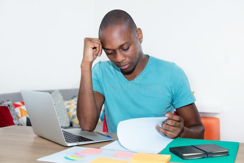 Adult african american man with laptop learning foreign language. At desk at home stock image