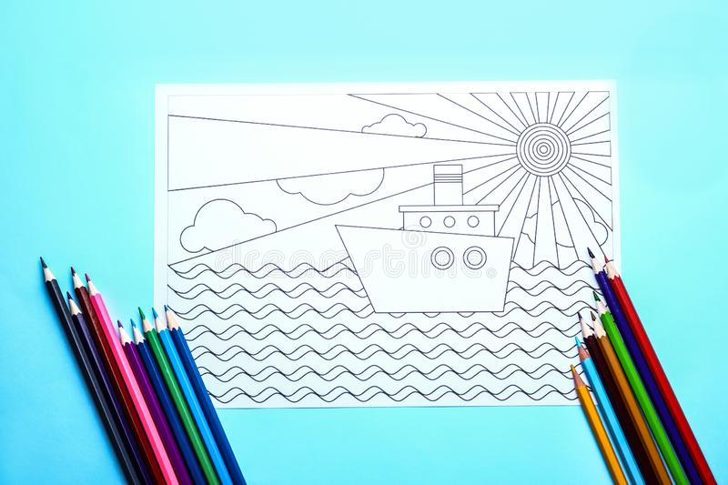 Adult anti stress coloring picture and pencils on table, top view royalty free stock photo
