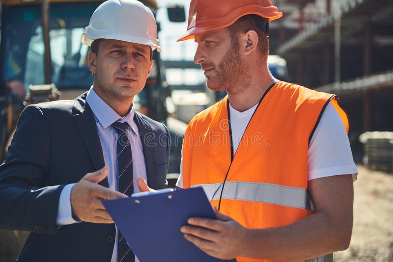 Adult architect is speaking with male worker royalty free stock photos