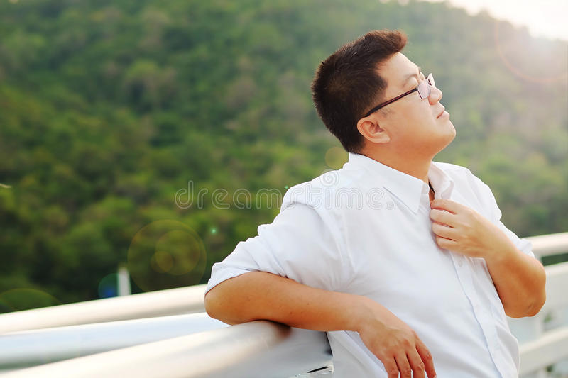 Adult Asian Fat man in white shirt feeling despondent from hard work be finding relaxing and meditation by make calm on the side royalty free stock photography