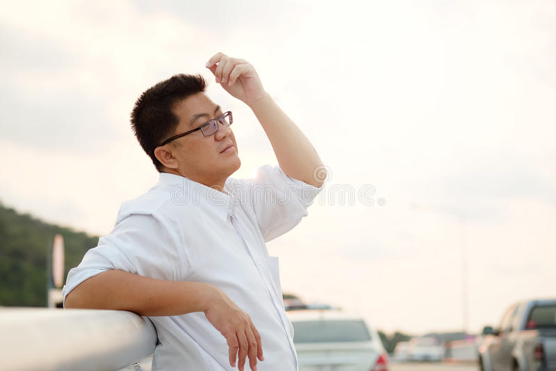 Adult Asian Fat man in white shirt feeling despondent from hard work be finding relaxing and meditation by make calm on the side stock photography
