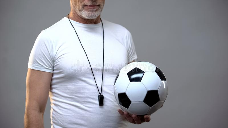 Adult athletic soccer coach holding ball, active lifestyle, sports activity stock photos