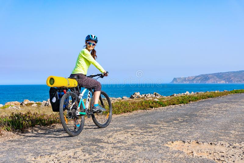 Adult attractive female cyclist riding her mountain bike by the ocean coast and looking back at the camera stock image