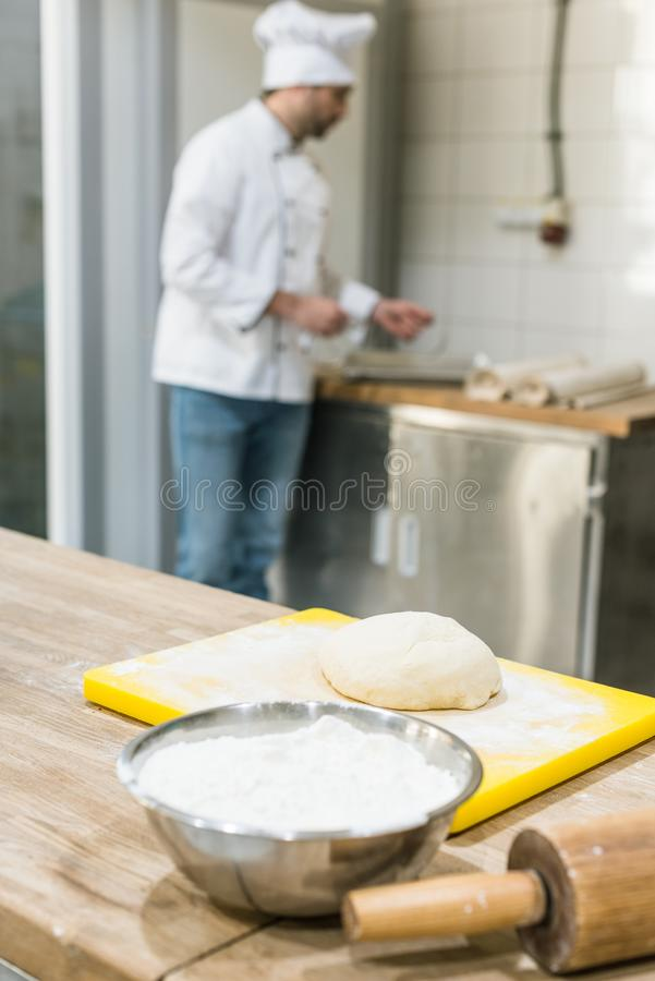 adult baker in chefs uniform preparing dough stock images