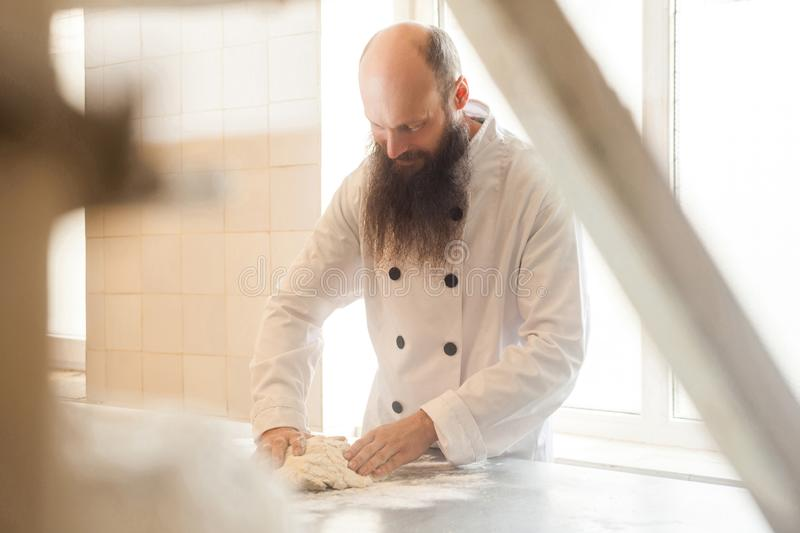 Adult baker with long beard in white uniform standing in his workplace and prepare the bread dough with hands kneading the dough. On table with flour powder stock image
