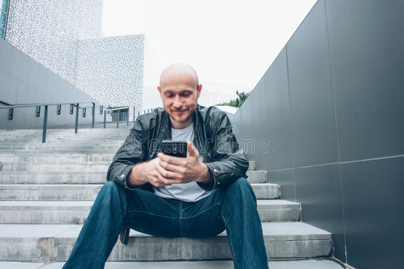 Adult bald bearded man using mobile and sitting in stair at city street stock photo
