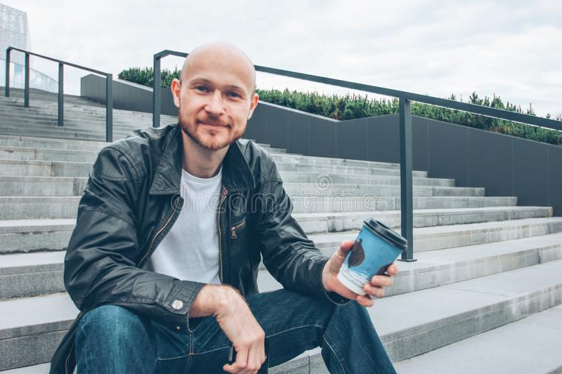 Adult bald bearded smiling man drinking coffee from paper cup and sitting in stair at city street royalty free stock images